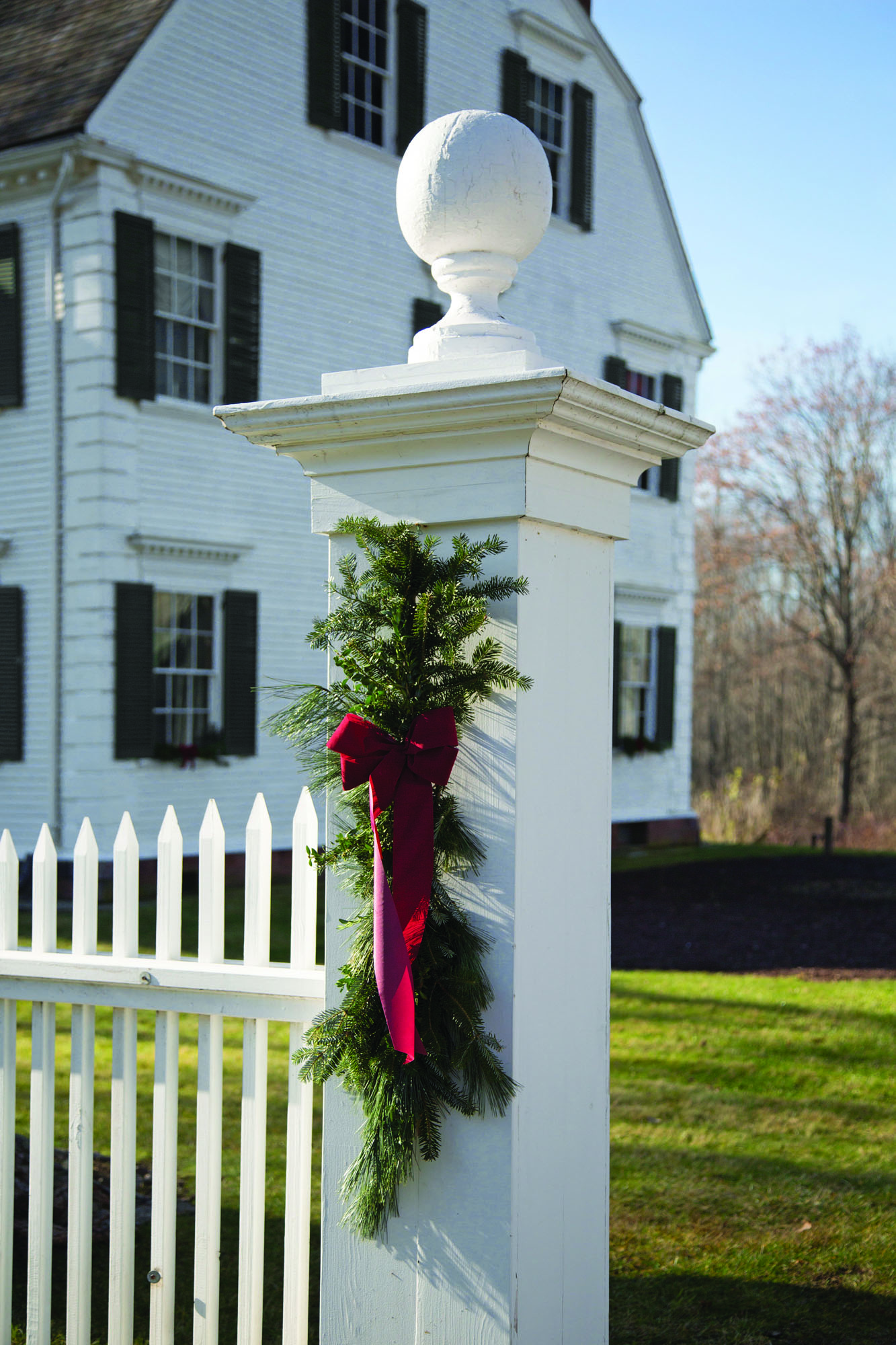 Simple, seasonal decorations include sprigs of balsam and white pine tips hung on a nail at gateposts.