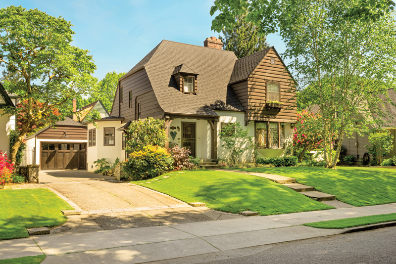 The detached garage echoes the roof style and materials of the original 1931 Tudor.