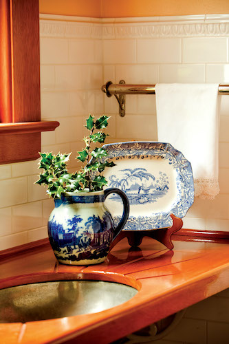 Blue-and-white china sits on a wide drainboard made from a church pew.