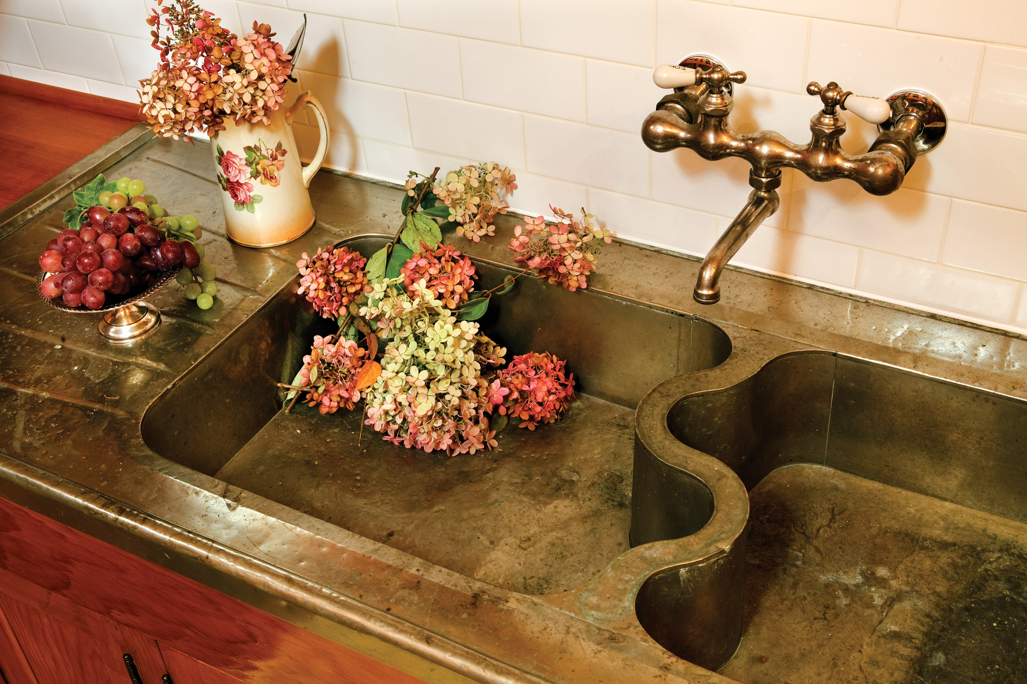 The antique sink of German silver (a copper–nickel–zinc alloy) has dents and patina.