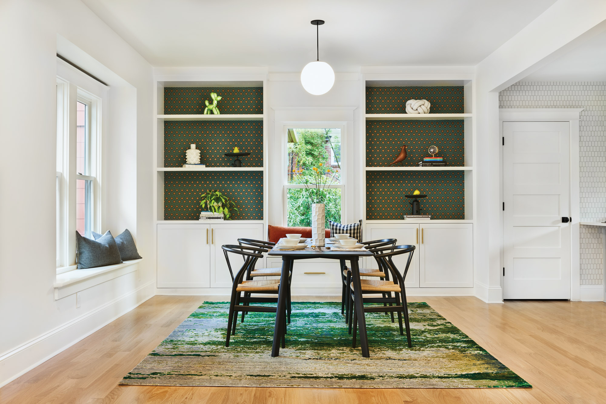 The open dining room is intimate due to paper-lined bookshelves, a window seat, and a handmade rug.