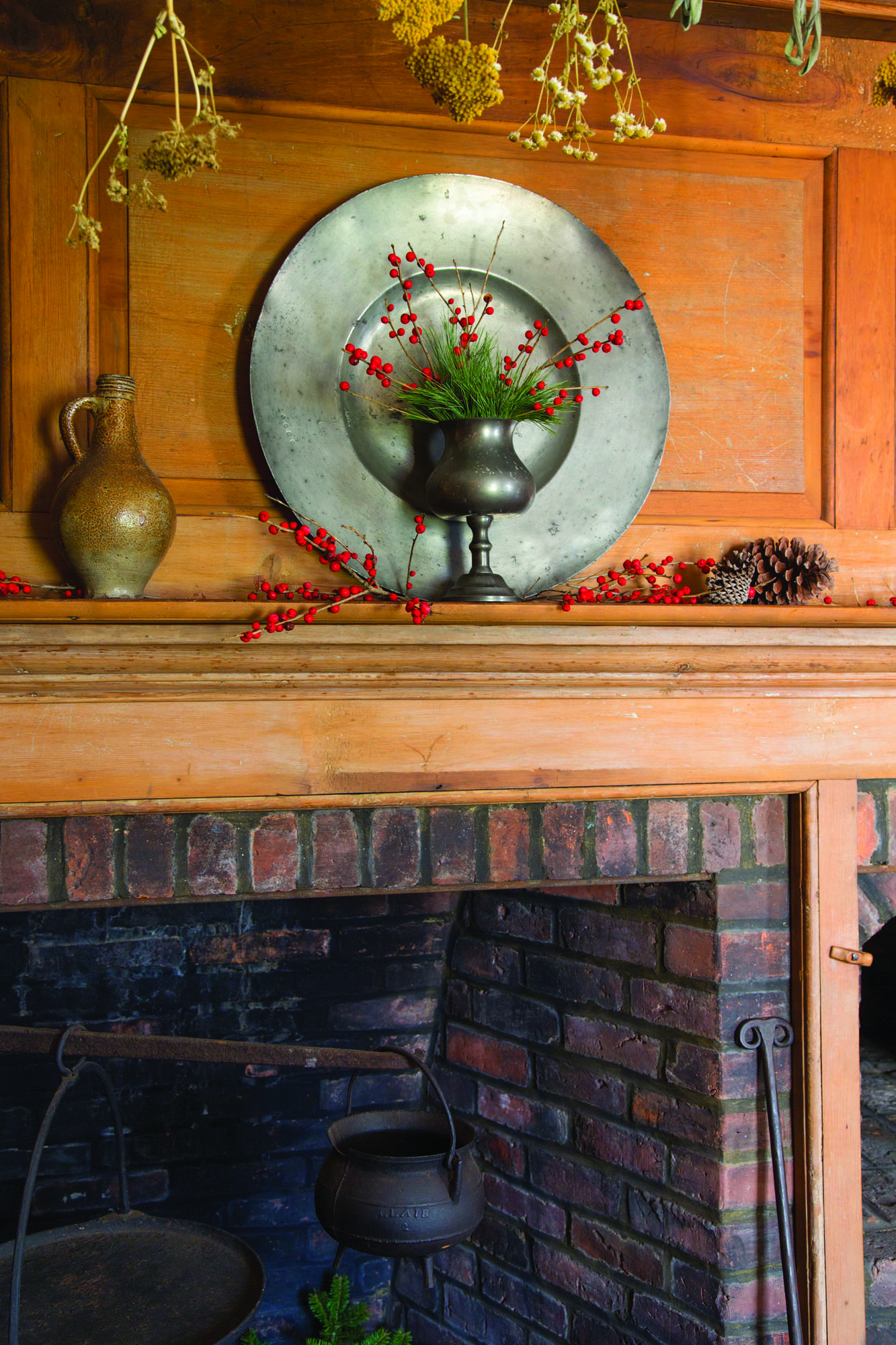 This fireplace, with its pine paneling and beehive oven, is in the 1760s Hearth Room. Herbs and yarrow from the autumn garden are hung to dry. Sprigs of winterberry holly give a pop of festive red against rustic wood and pewter plates. This holly variety is native to Connecticut.