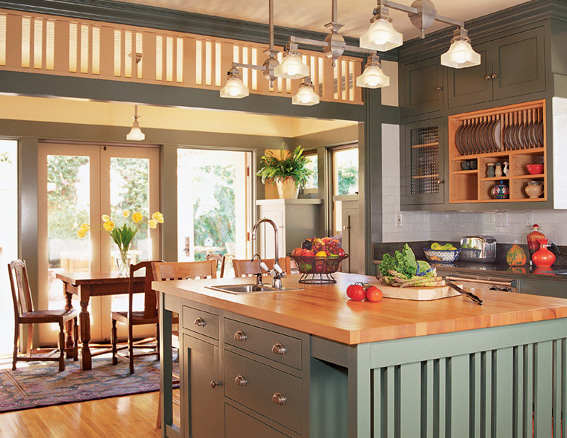 Finished in soft green and cork orange, the Prairie Revival kitchen flows naturally through a porch-like breakfast room to an open-air terrace. Mission-style lighting brightens the butcher block-top island.