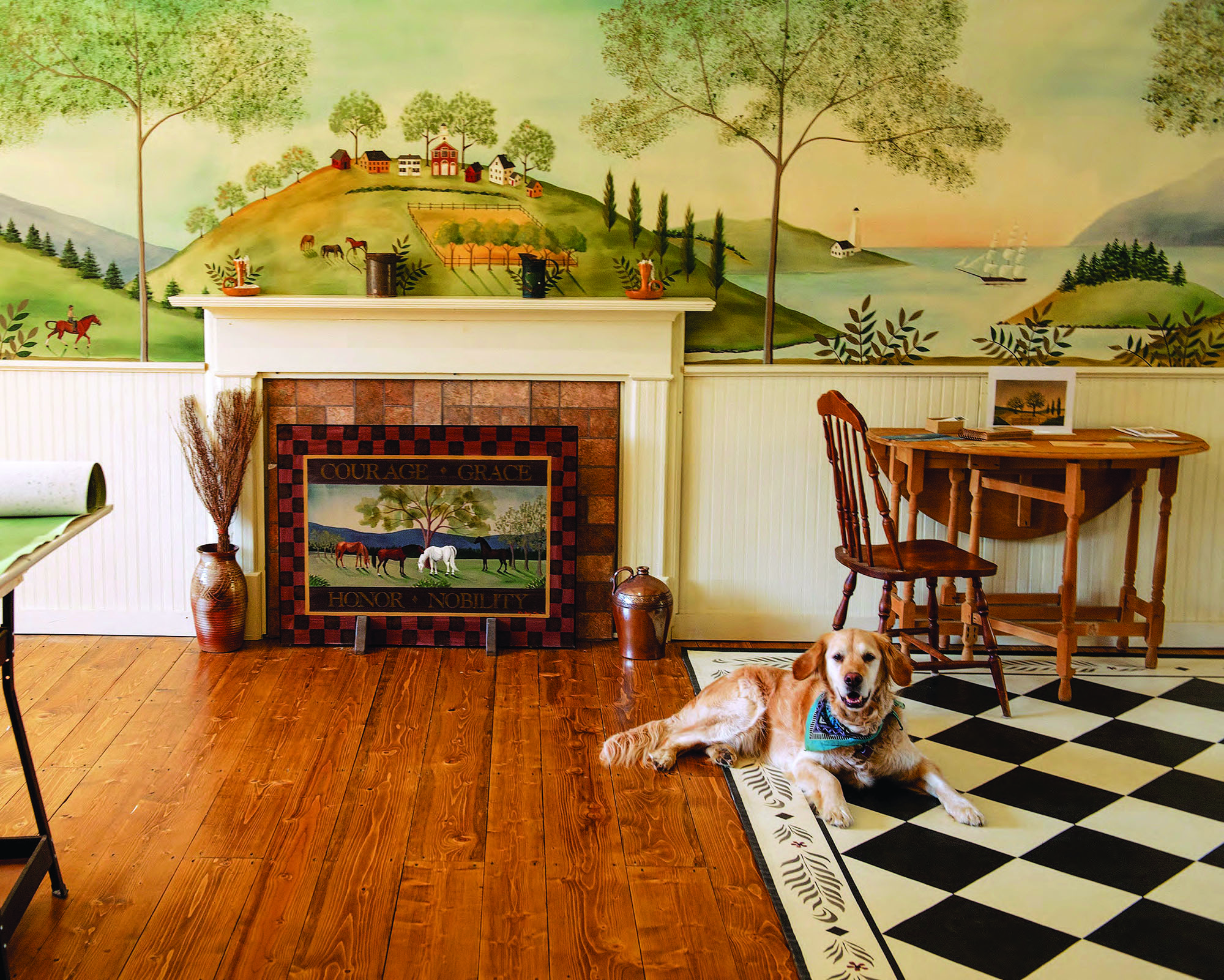 A hand-painted pastoral fireboard by Lisa Curry Mair of Canvasworks Designs complements a mural by the same artist.