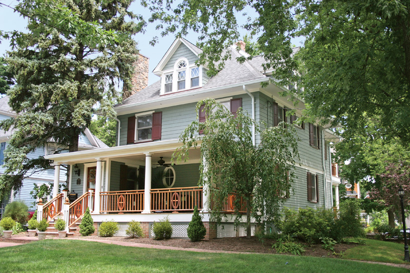 The restored open porch does justice to the Colonial-style Foursquare, which boasts a Palladian window in its dormer.