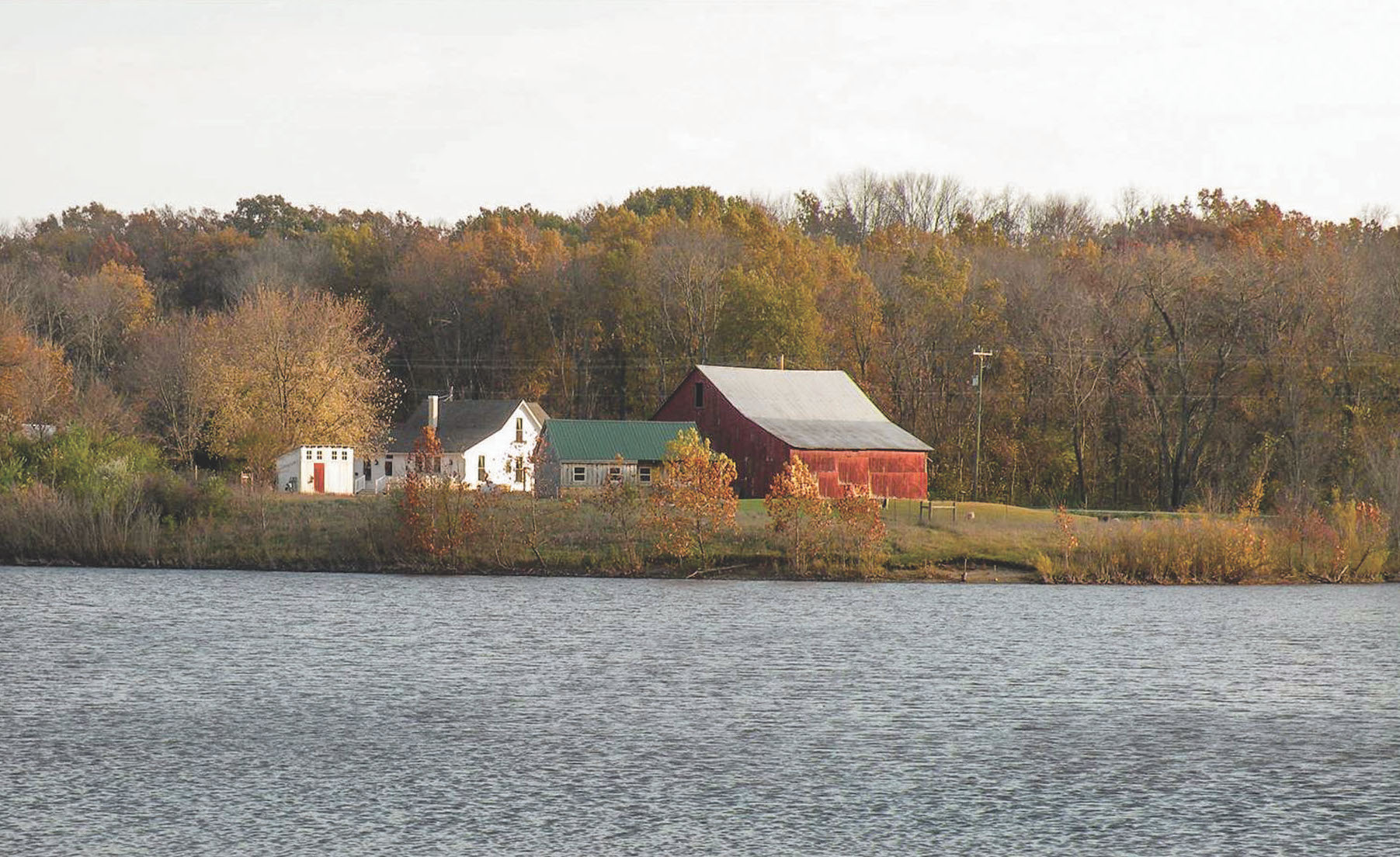 From a pond on adjacent property managed as a public park, the view toward the farmstead is bucolic.