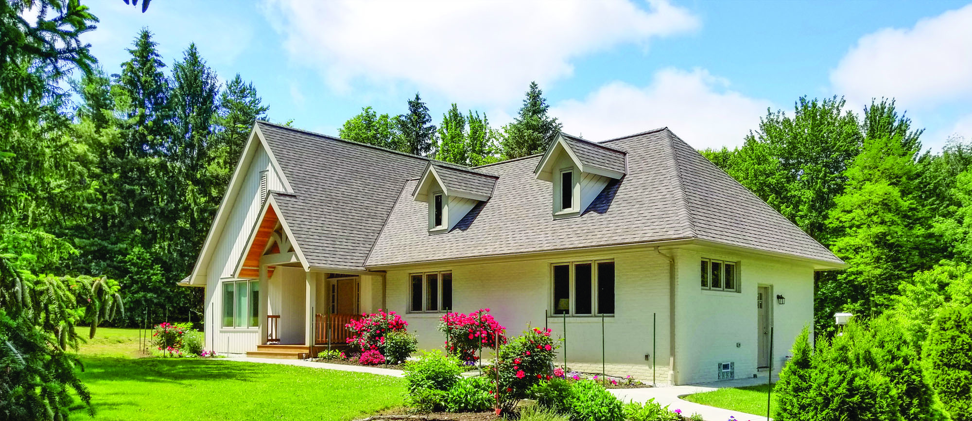 A steeper roof adds space and style; the pretty entry has a practical overhang.