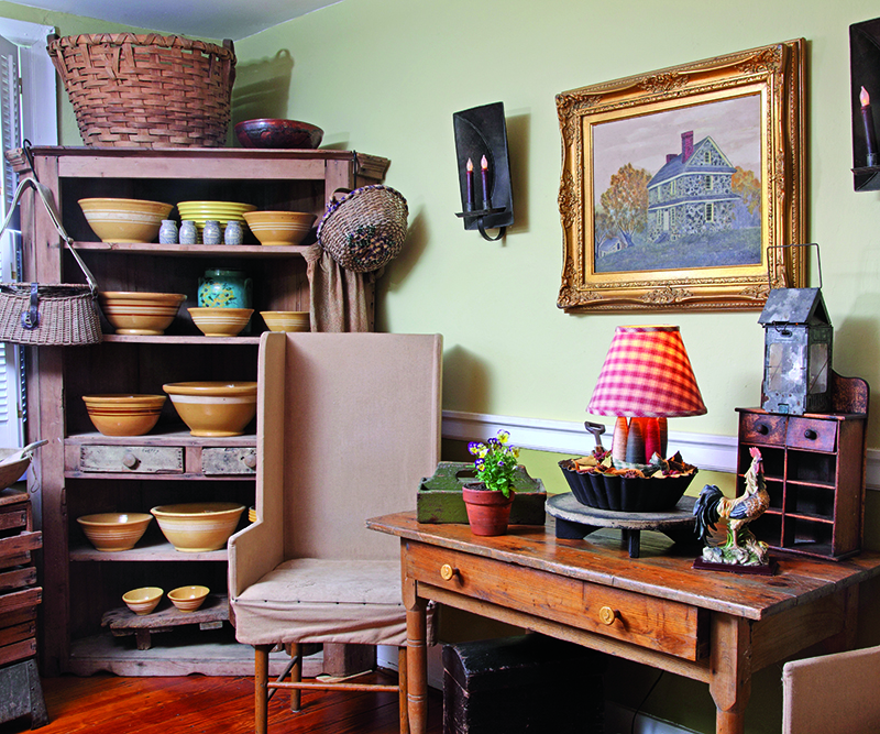 Near the kitchen in an early house, a dining nook is cozy with wing chairs and an antique flat-backed cupboard displaying yellowware bowls that pop against the unpainted wood.