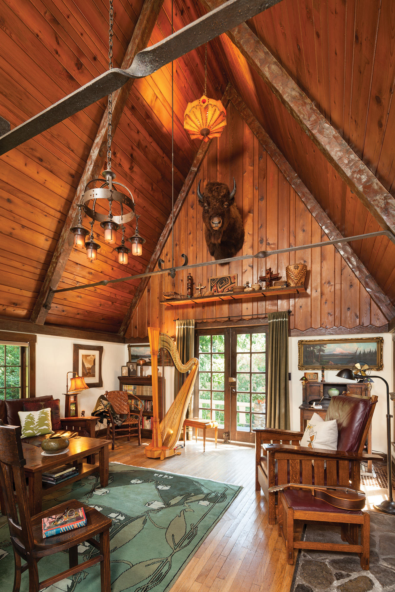 The 20-foot-tall great room fills the southern end of the home. A comfortable mix of furnishings includes a leather Morris chair and an original Gustav Stickley rocker.