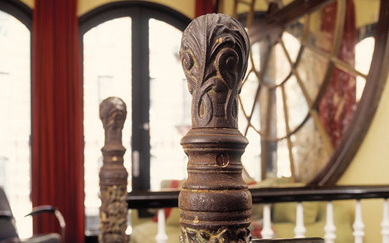 Two Victorian cast-iron newel posts anchor a wood balustrade.