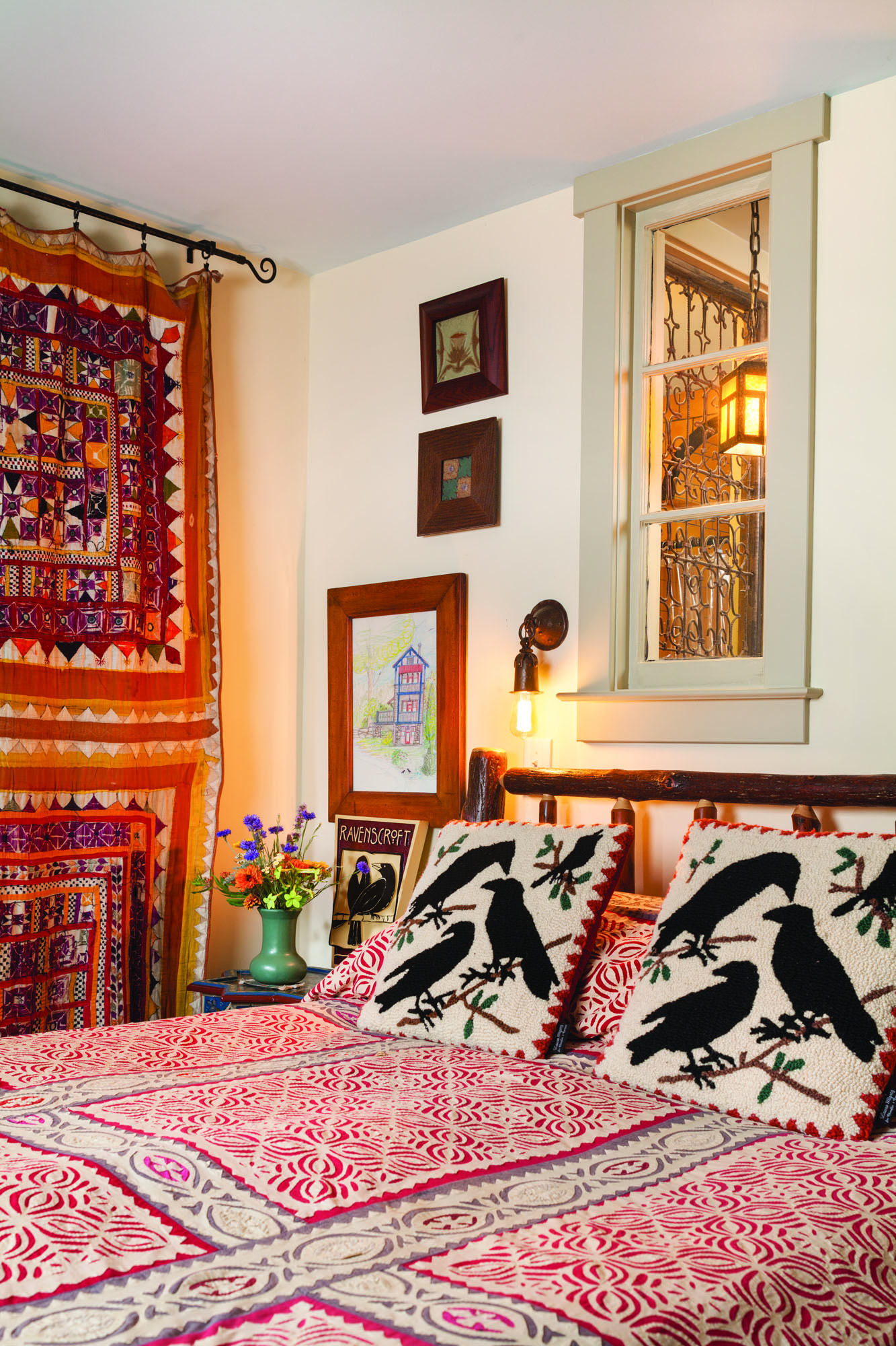 Mixing what's local with the exotic, the lowest-level guest bedroom is a departure that still features handcraft. The hand-embroidered hanging from India is vintage. Salvaged windows above the bed let light into the Moorish bathroom beyond.