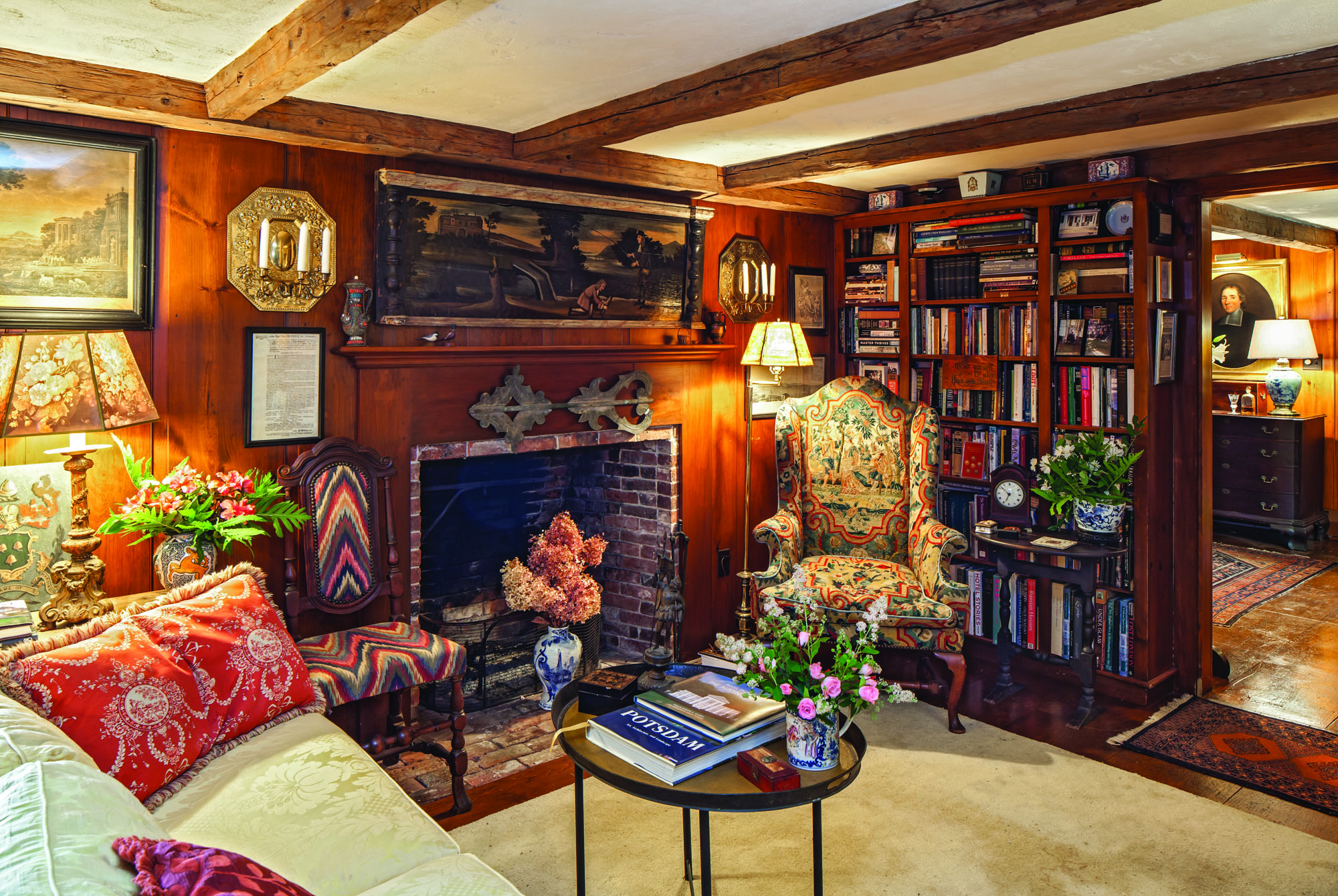 Above the fireplace in the library hangs a 1690 overmantel painting from Maryland, featuring marbleized mouldings and turnings. Below it is a fragment of a 19th-century banner weather- vane. The sconces are Dutch, and the wing chair upholstered in needlepoint dates to 18th-century England. The smaller chair, with flame-stitch upholstery, was made in Boston in 1700.