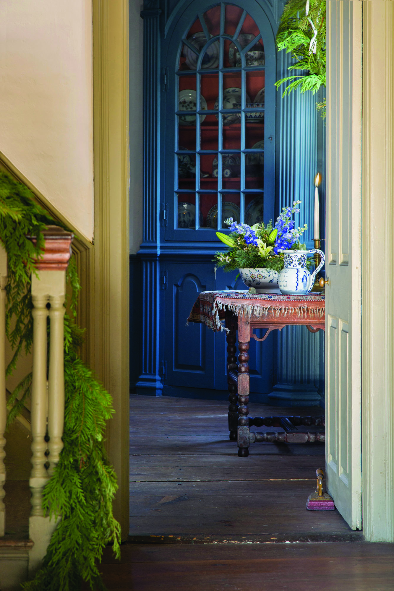 The less formal staircase in the 1760s Georgian block is swagged with plain greenery. Through the doorway is a glimpse of the Burbank parlor, with its classical corner cabinet featuring fluted pilasters and an arched, multi-light door.