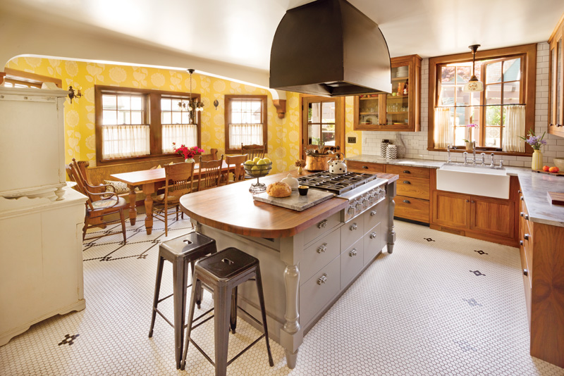 Cabinets and tile are old-fashioned; the island work table is painted grey.