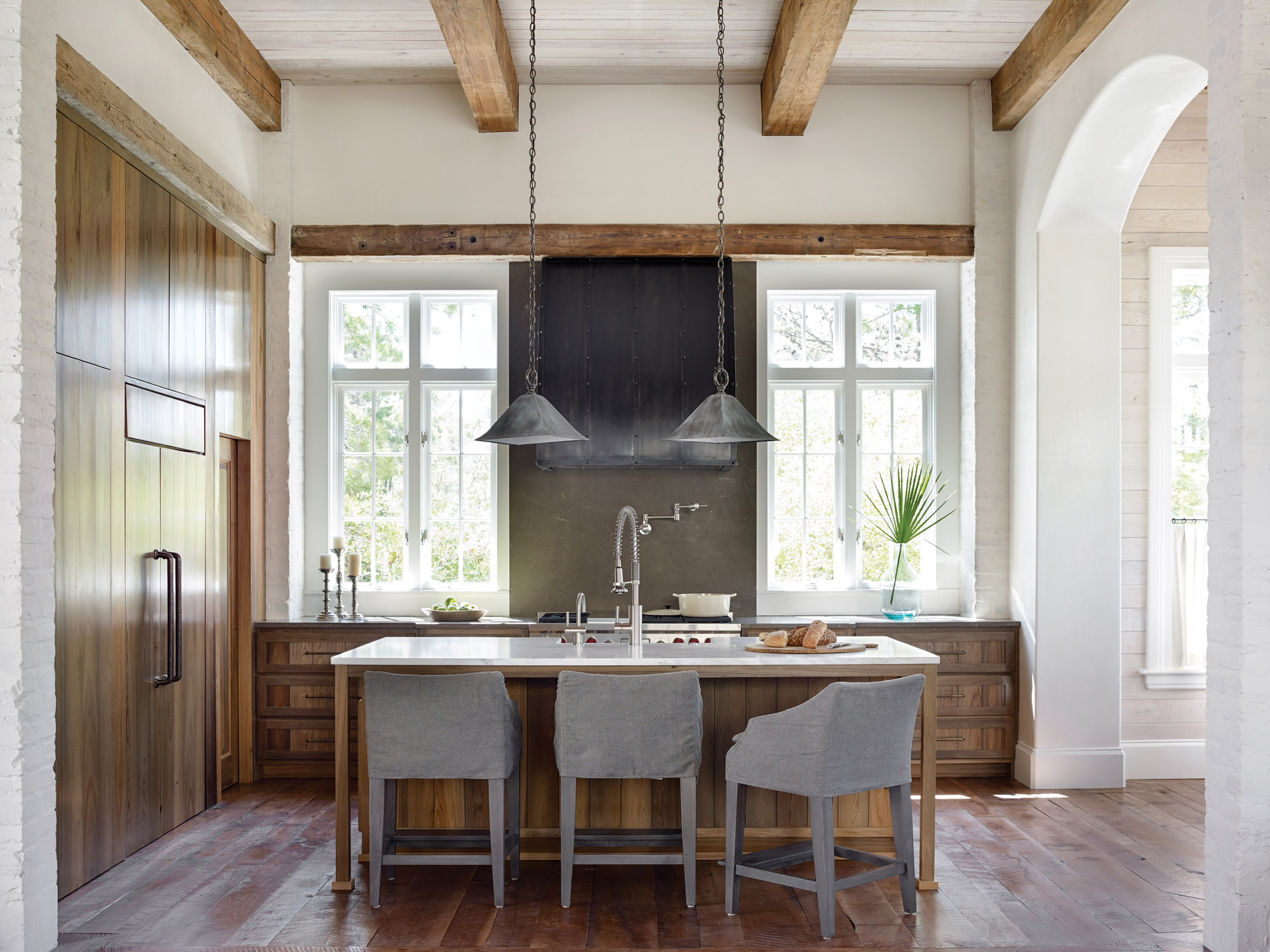 The  kitchen's beams and cabinets are made from reclaimed cypress.