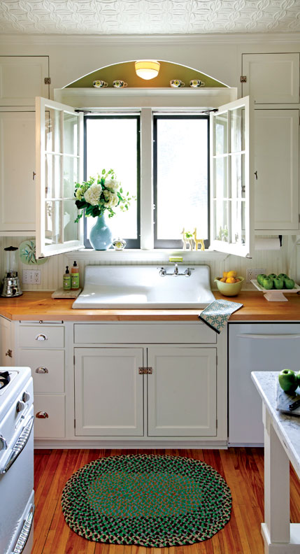 Salvaged casement windows, butcher-block countertops, and an antique sink lend a sunny air to the tiny kitchen.