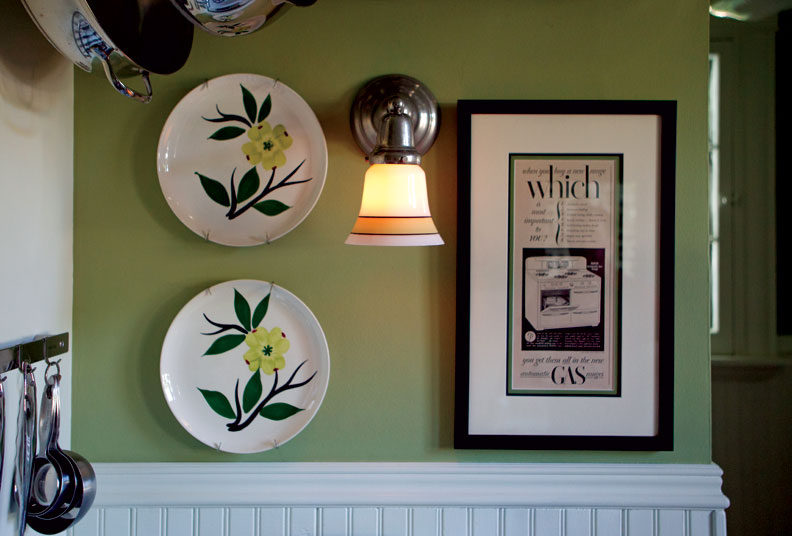 A reproduction light fixture mingles with vintage Stetson Pottery and an ad depicting the 1948 Roper range.