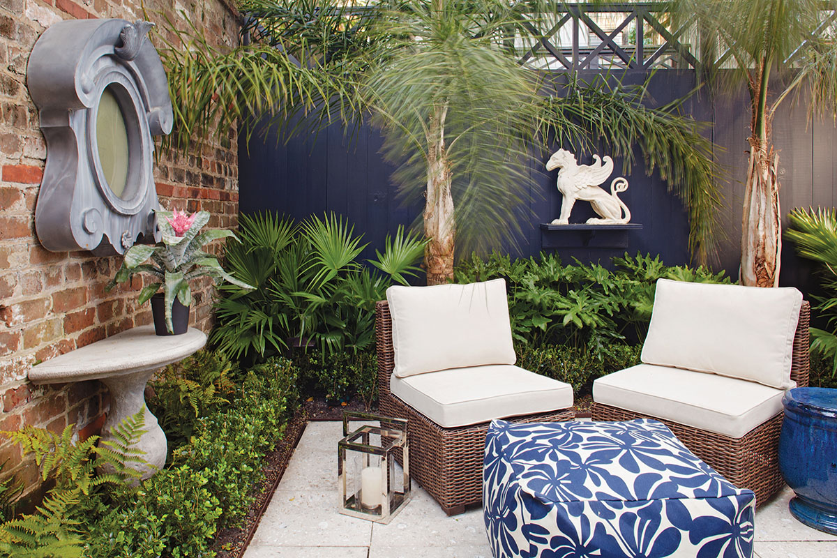 The courtyard is furnished as an outdoor room, with a pair of comfy chairs, a pouf in a floral pattern, and a glazed garden stool that doubles as a side table.
