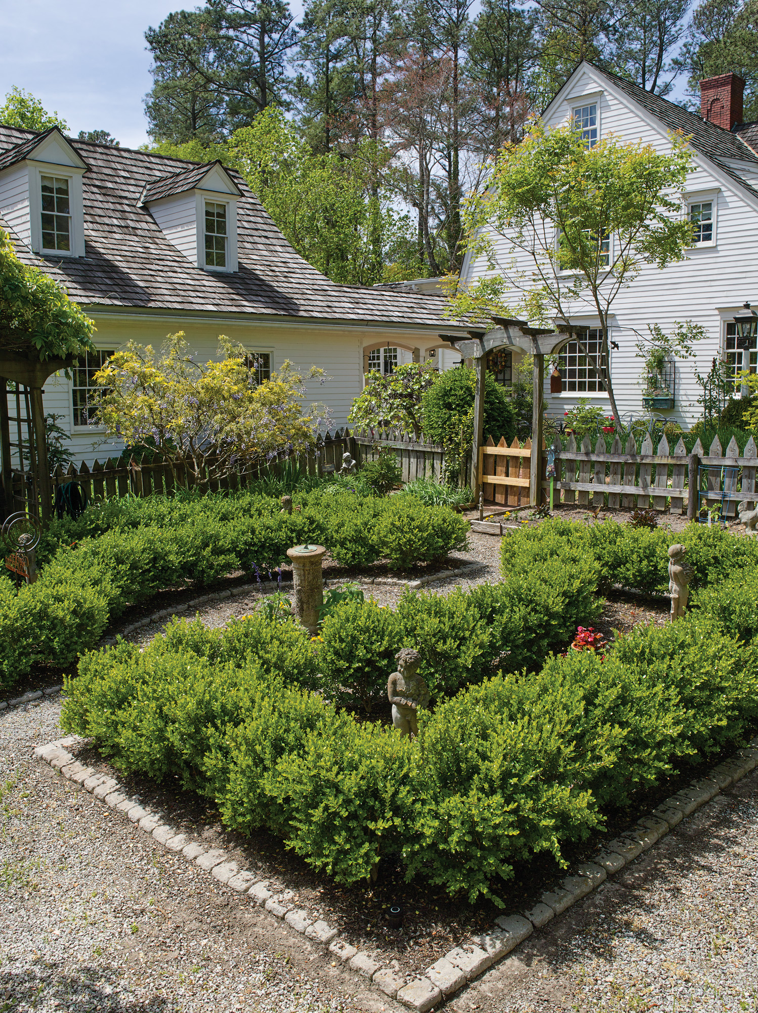 A formal garden ties the garrison Colonial to the garage and breezeway.