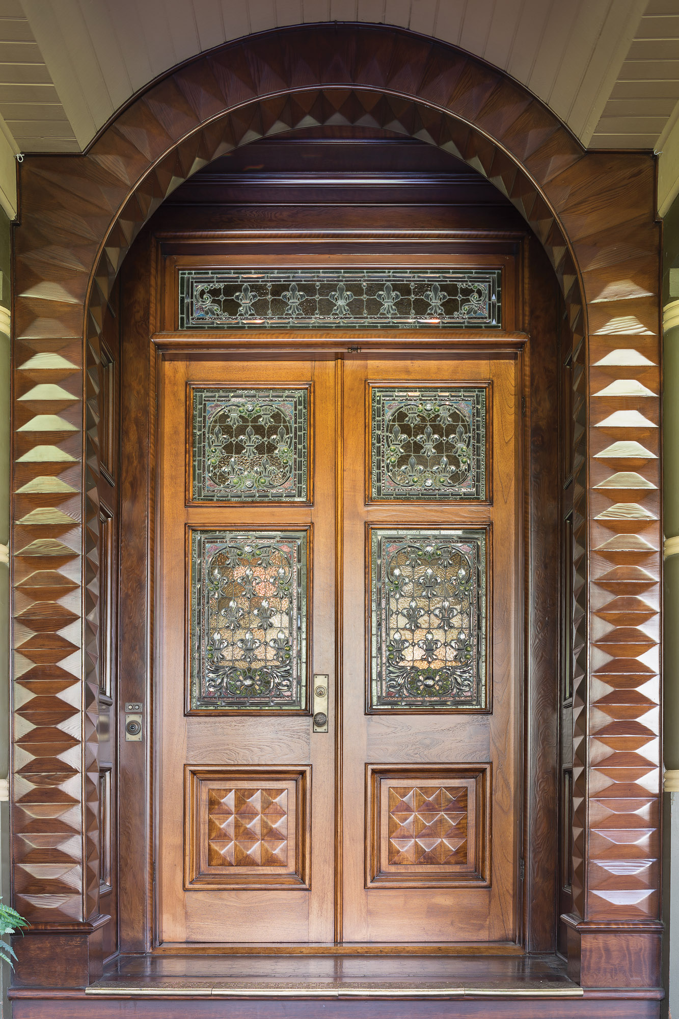 With ornate beveled glass, the front door is a tour de force set within a carved redwood archway.