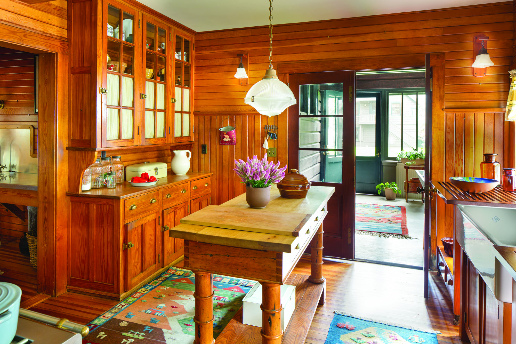 Tongue-and-groove paneling is original to the house, and a fitting envelope for the kitchen that was rebuilt according to its 1915 intentions. The tall cabinet is original. A big worktable sits in the middle; other cabinets are on wheels.