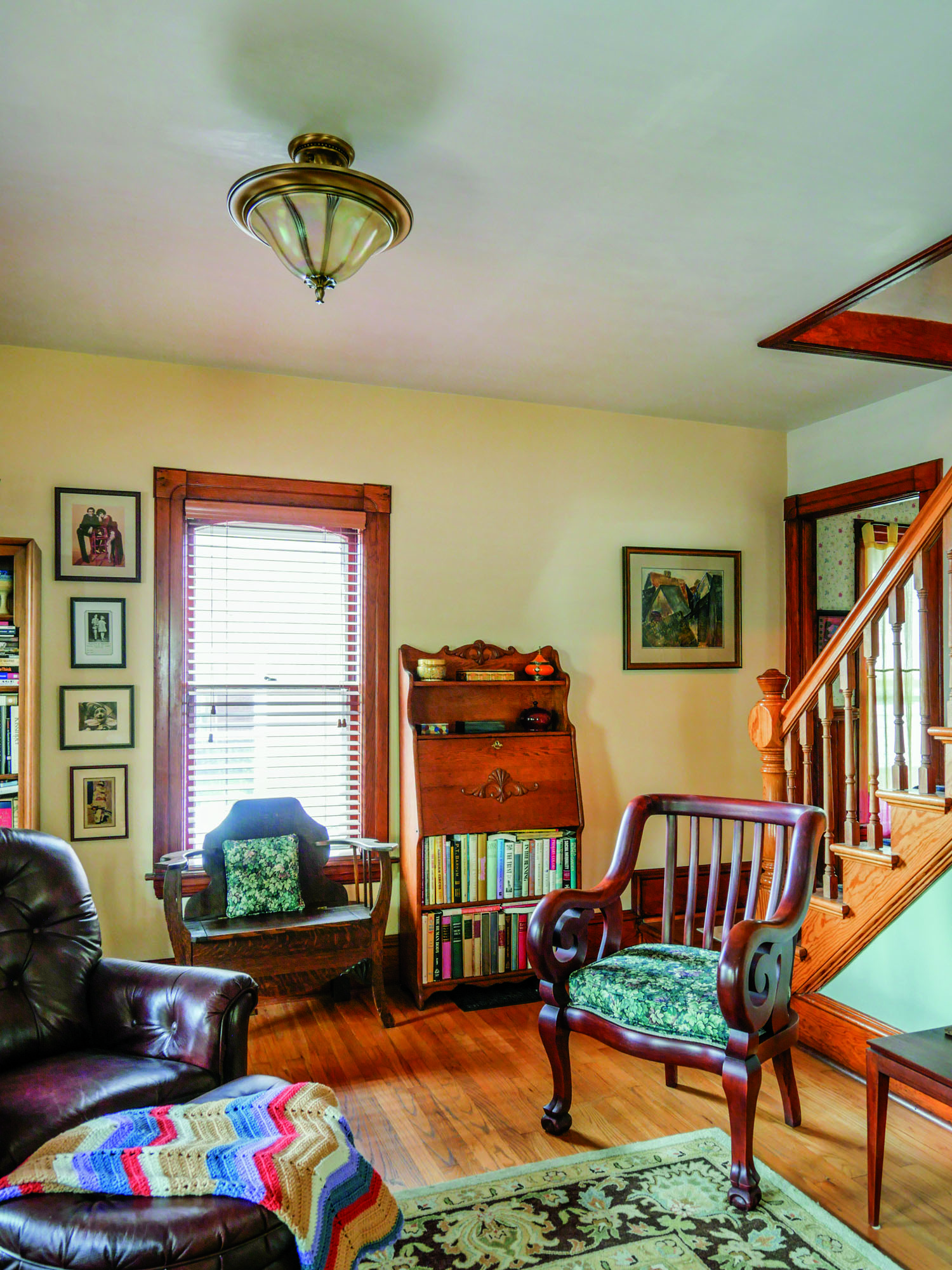 The living room is comfortably furnished in an eclectic mix of family pieces and antiques. Flooring and woodwork are original.