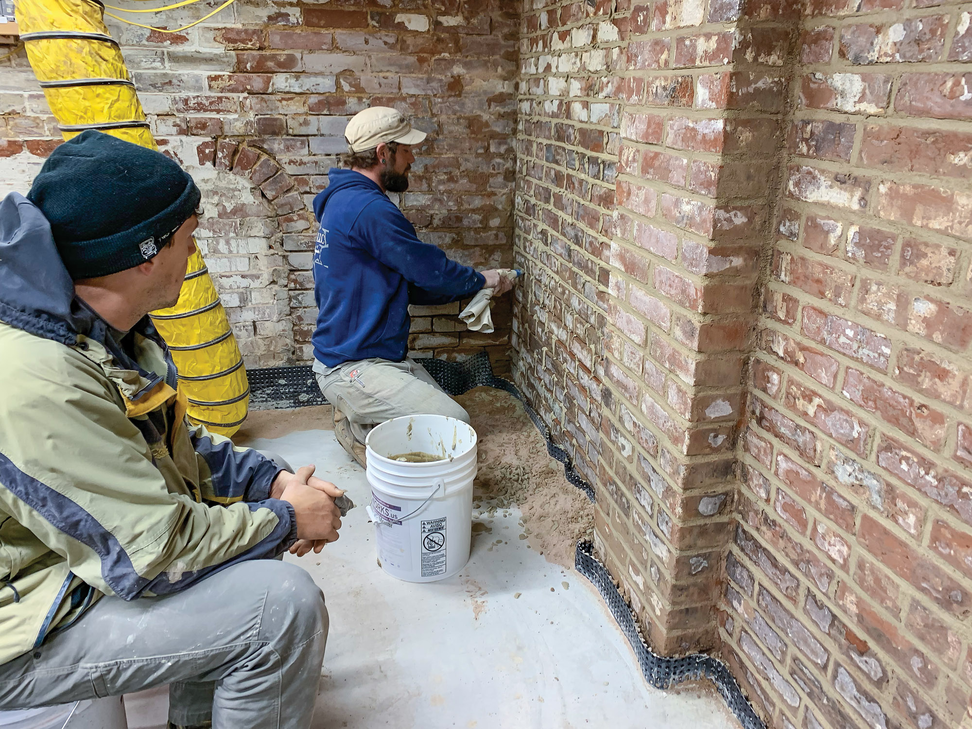 Although repointing is traditionally done with a pointing trowel, many contemporary masons use a squeeze bag to fill joints. While the mason works, author Alex Santantonio rests from his paint-stripping labors.