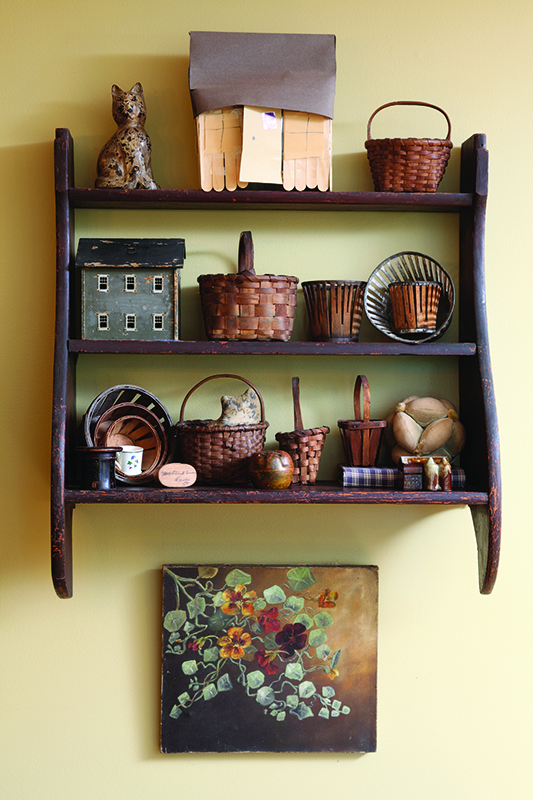 A petite 19th-century whaleback set of shelves holds a collection of tiny treasures in an owner-built replica Cape.