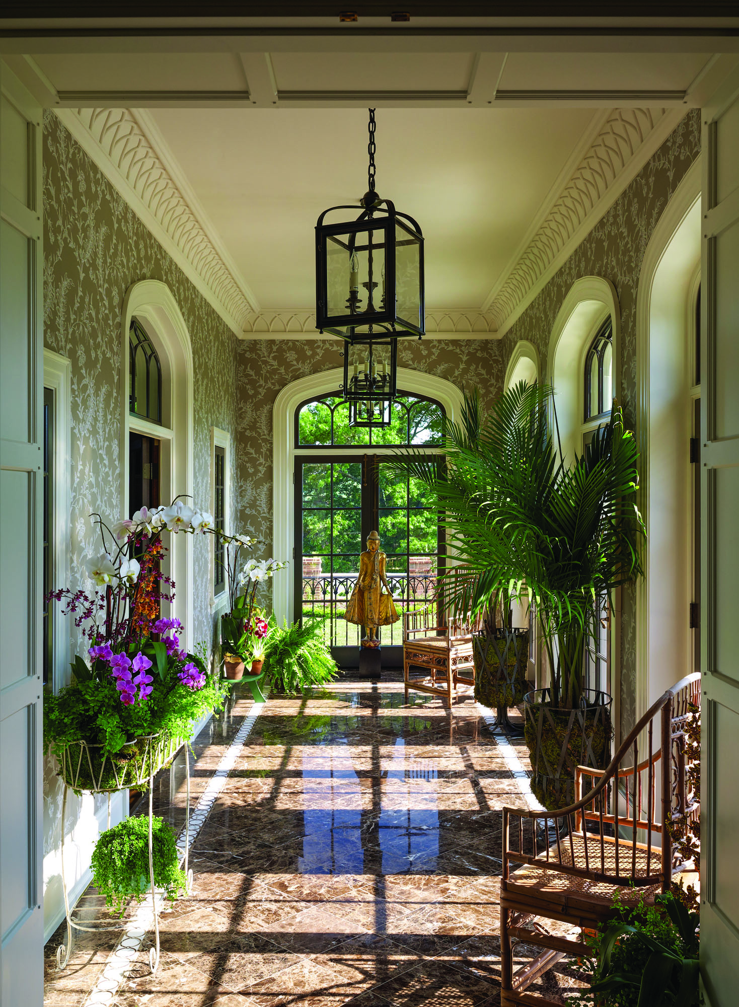 The orchid room is flooded with light from four pairs of doors crowned by Tudor-arched transoms with muntins that mimic Gothic tracery.
