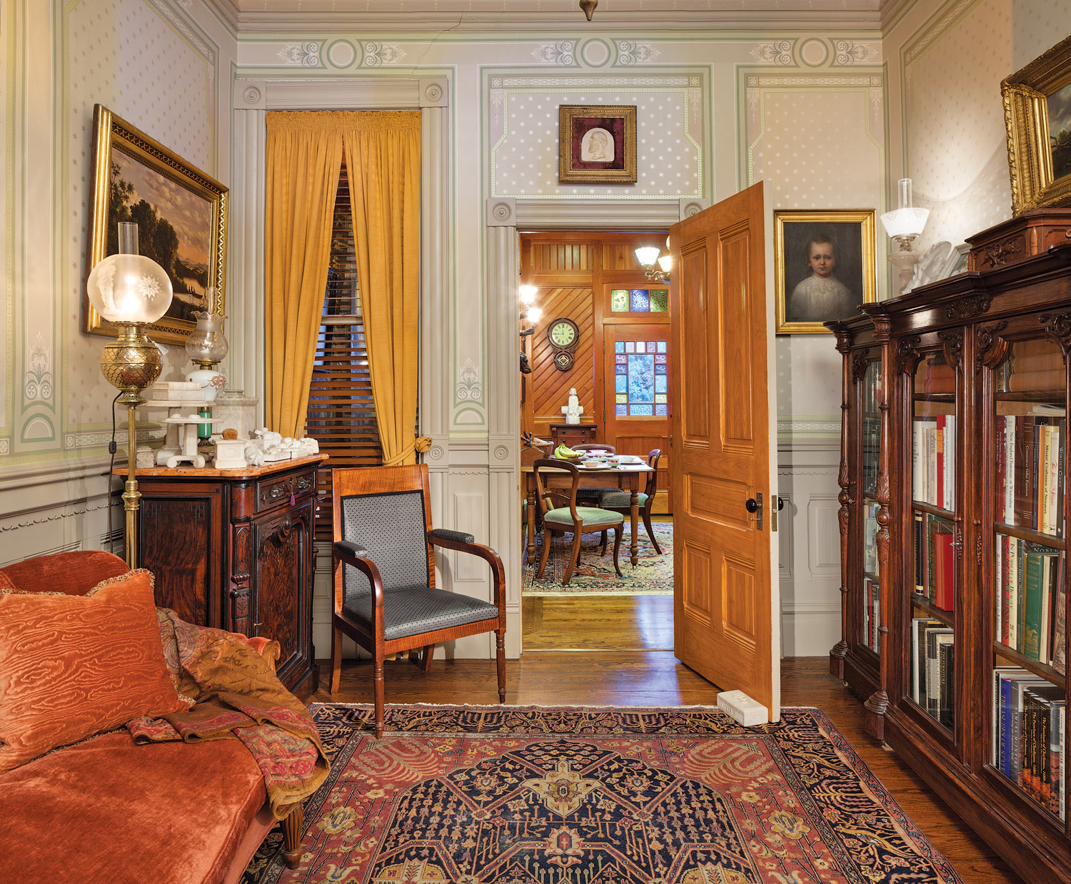 Decorated with Renaissance Revival furniture and Bradbury & Bradbury's Victorian-era 'Neo-Classical' papers, the front parlor is the most formal room. The Aesthetic Movement kitchen is beyond the door.