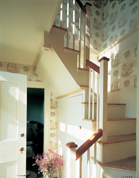 Colonial-style wallpaper lights up a stairwell in a summer house in Maine.