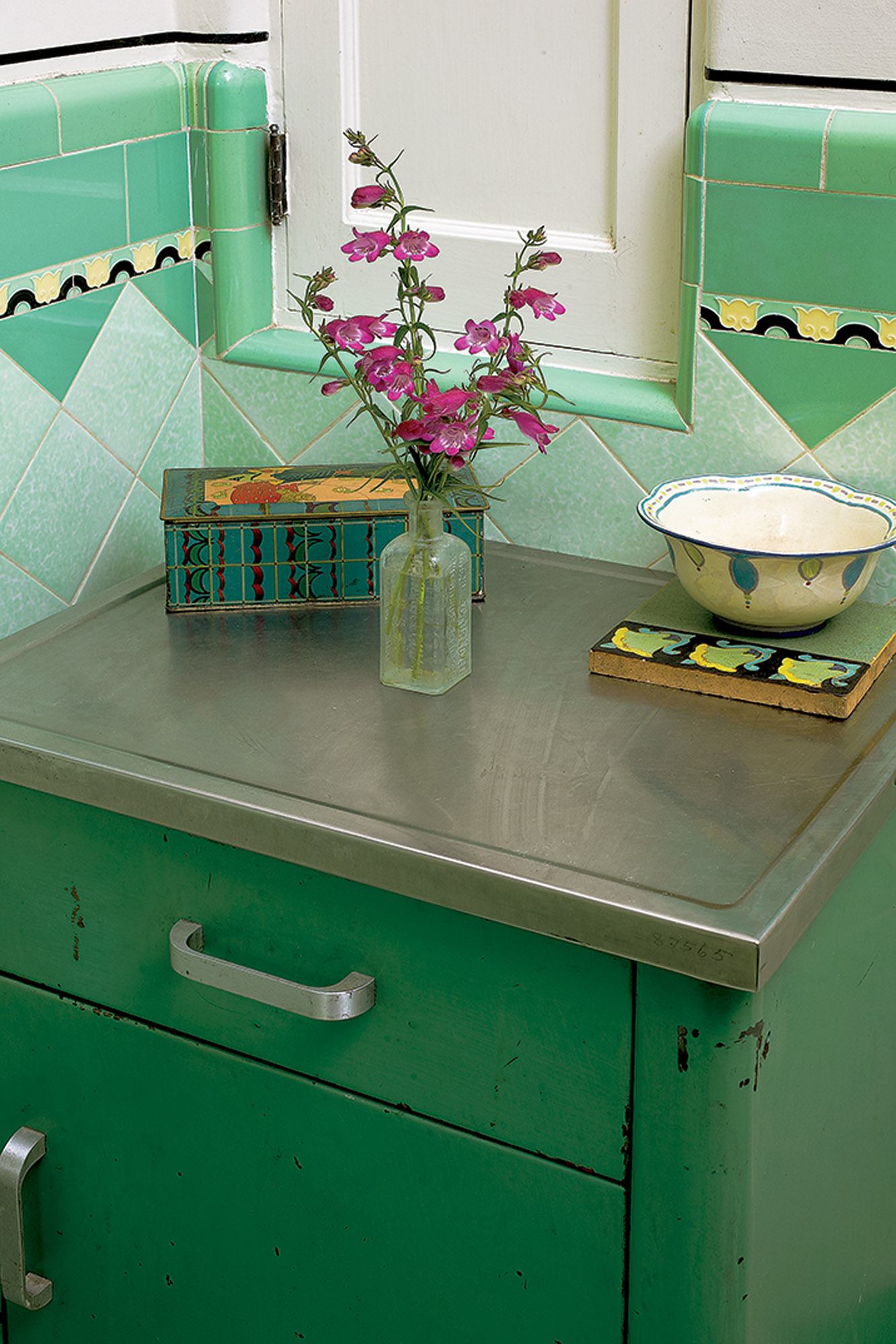 """The tile design and bullnose trim are obvious in this corner, where a """"shortcut"""" door opens into the hallway linen closet. The green metal cabinet, likely from a medical or dental office, was a flea-market find."""