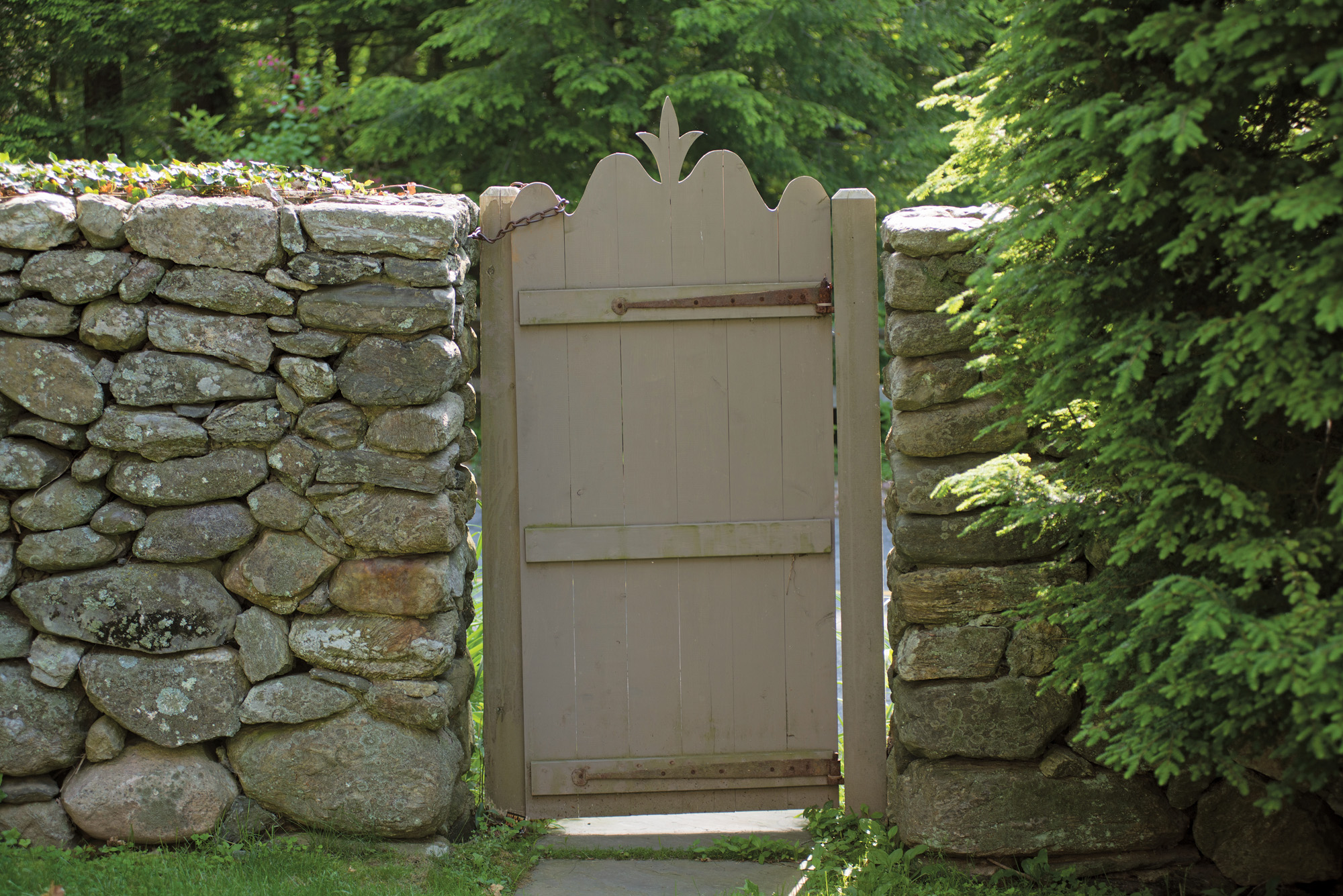 A wooden gate gives access to the stone-walled enclosure.