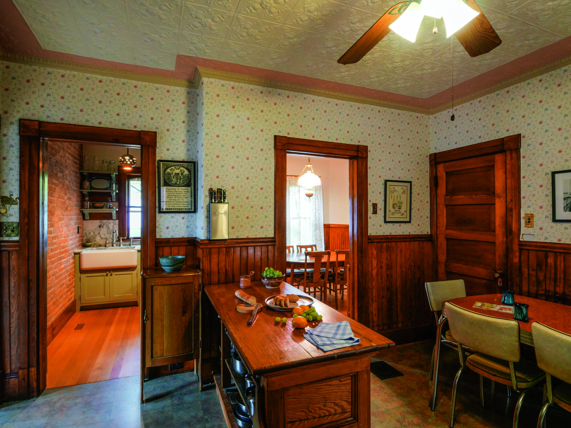 The kitchen is airy and old-fashioned with a stove at far left, a worktable as an island, and a small dining area to the right. With a big sink, the butler's pantry functions as a scullery.