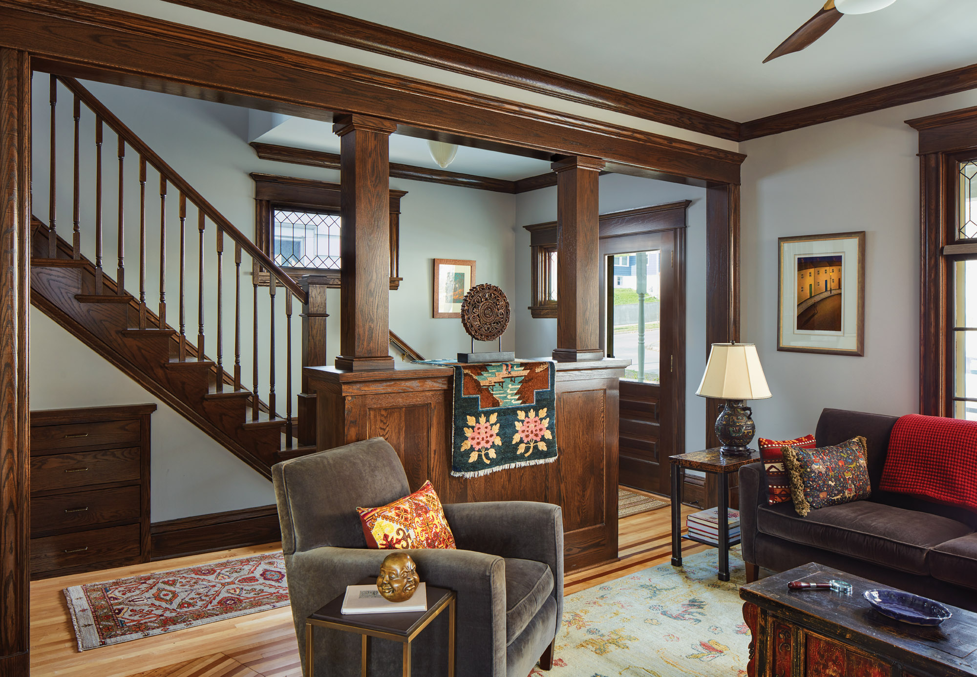 """With a colonnade and open stair, the entry is dramatically improved. Using millwork from a local lumberyard kept new work """"in the vernacular."""""""