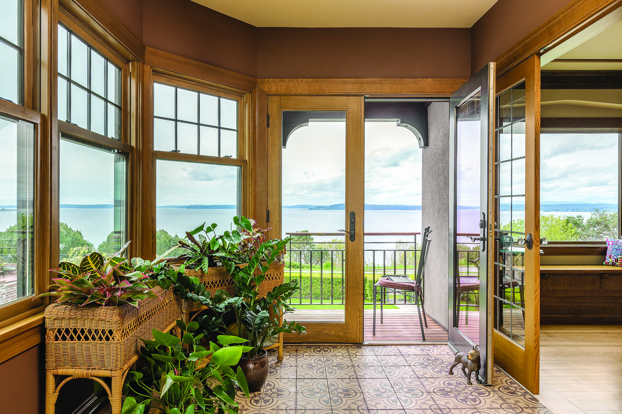 The sunroom faces southeast with windows on three sides, taking full advantage of the view. Floor is concrete tile.