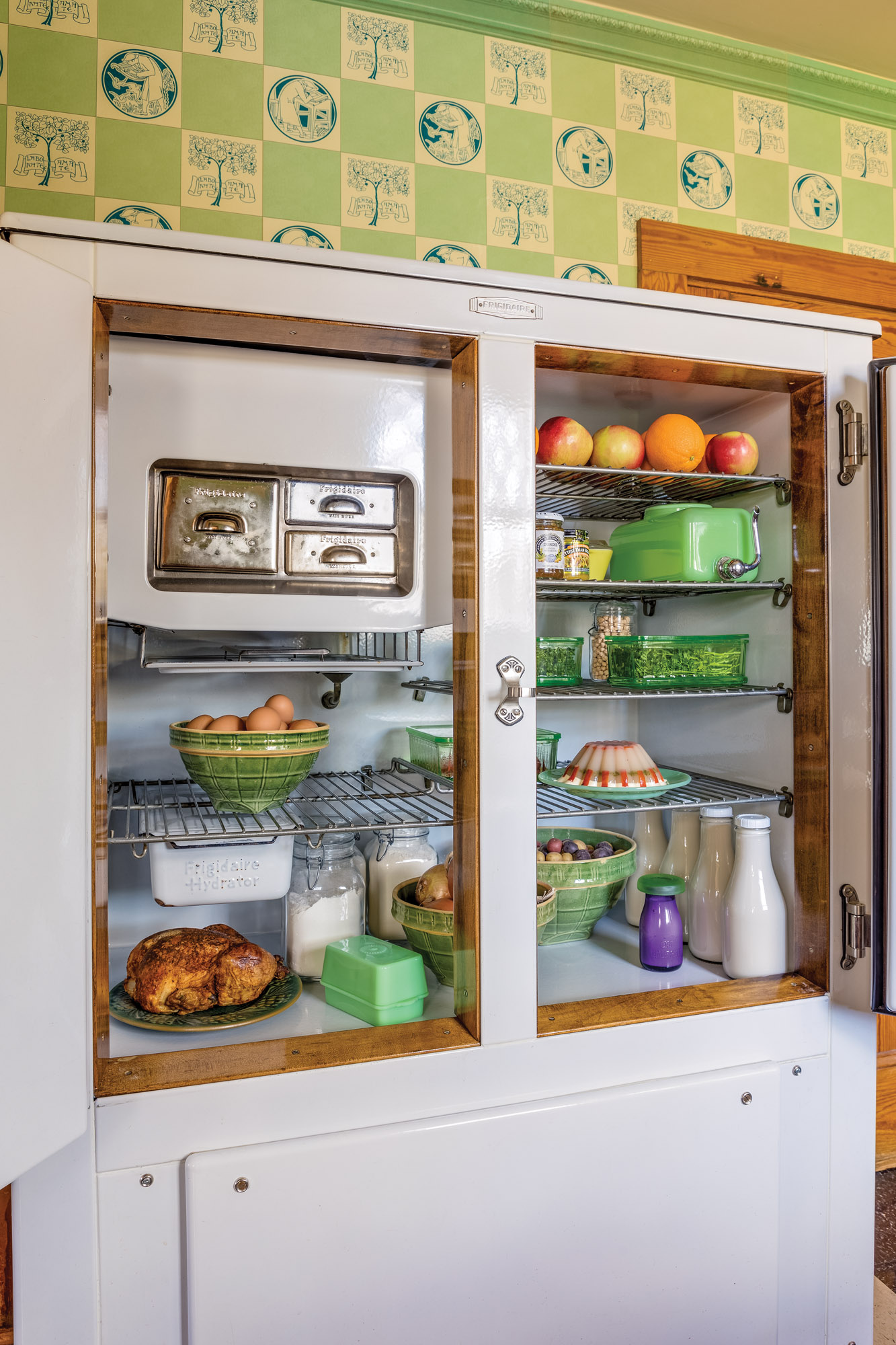 The ca. 1929 Frigidaire was converted for modern refrigerant. McKee Jadeite, McCoy bowls, and Hazel Atlas glassware are vintage.