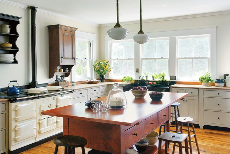 A soapstone sink and a central worktable lend authenticity to a farmhouse kitchen.