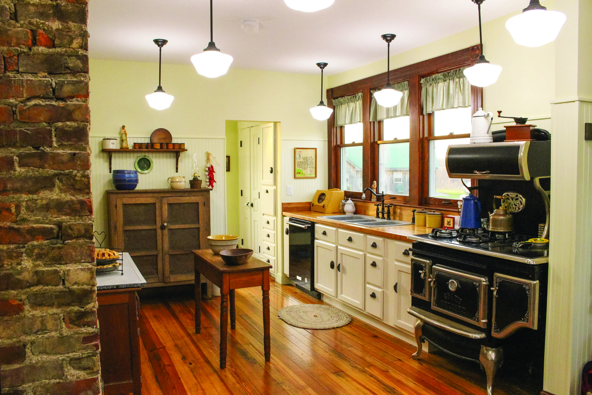 With a wall opened up, the kitchen is larger and more functional. The range that looks like a woodstove is actually a modern reproduction.