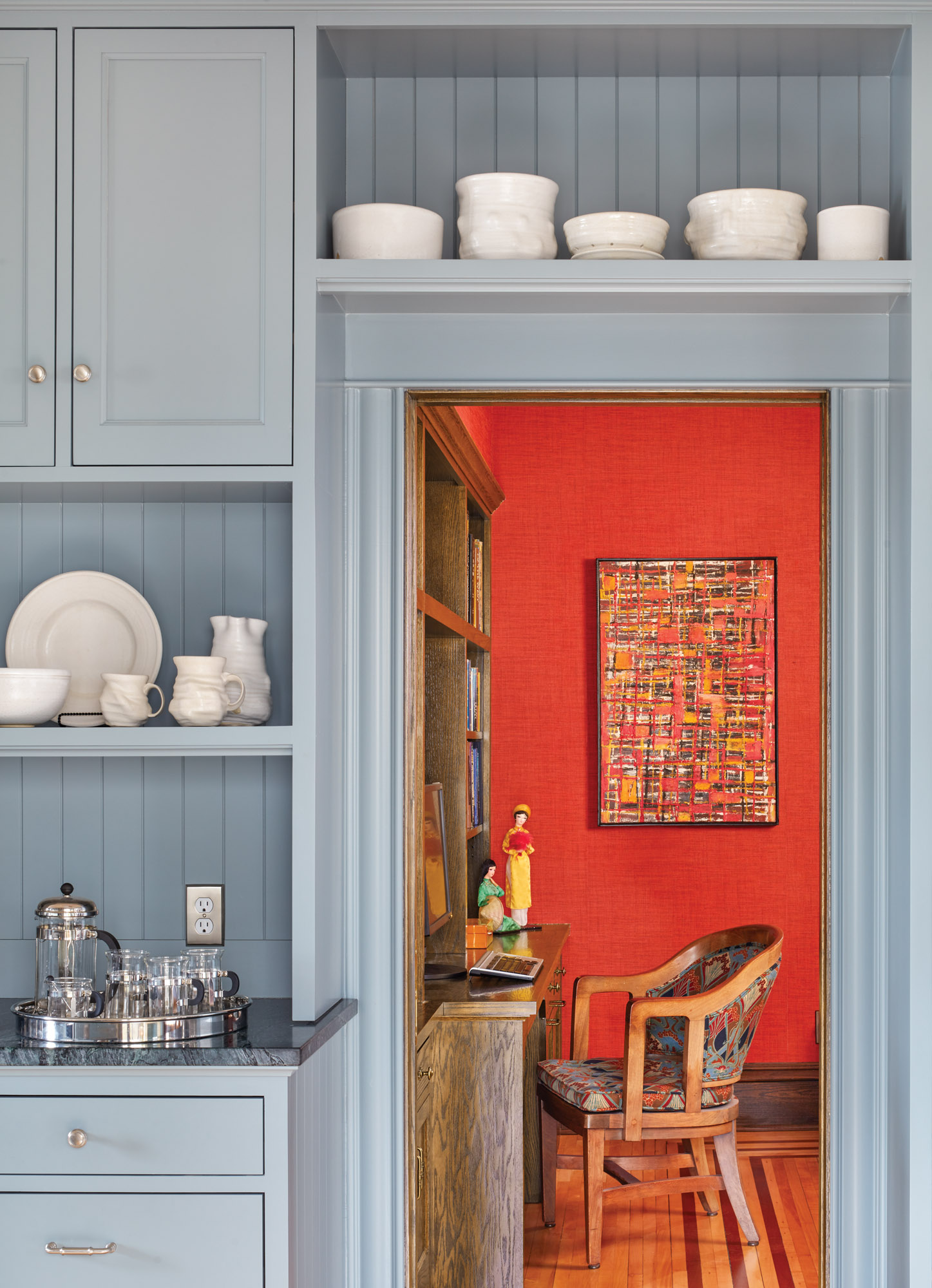 Separated from the kitchen by a pocket door, the family room now has a wall of oak built-ins. The modern grasscloth wallcovering is a warm complement to the blue kitchen cabinets.