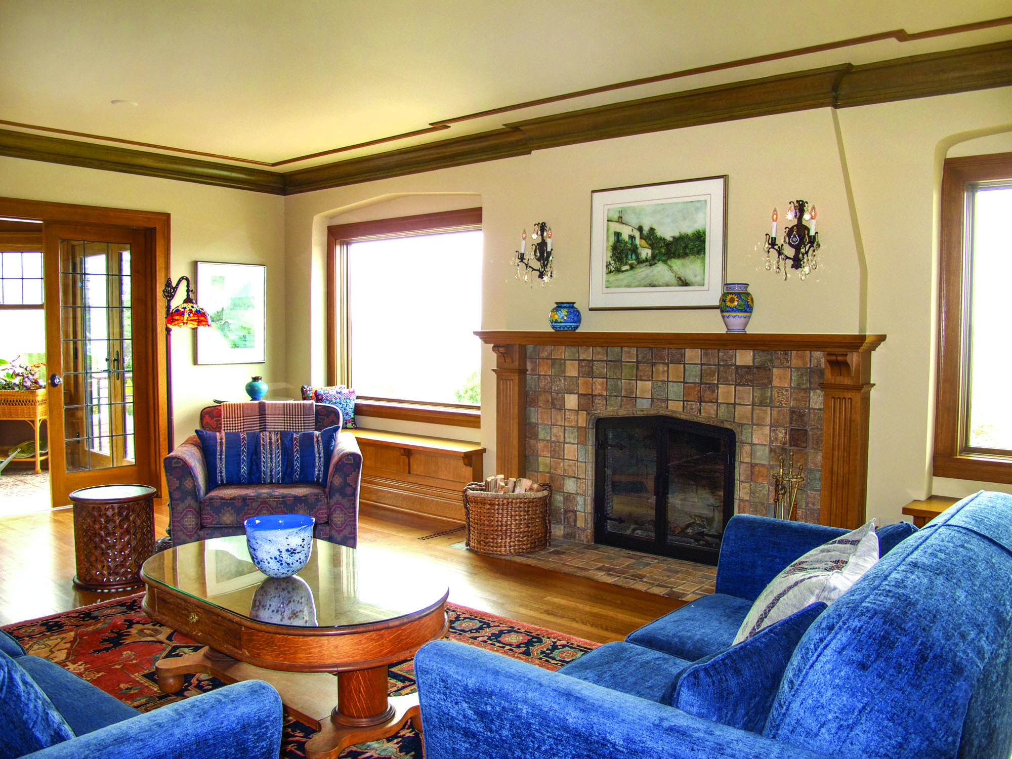 The original Batchelder fireplace and arched window wells in the living room are original.
