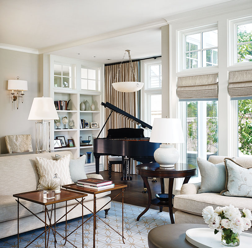 The living room has a gracious piano alcove. Transom windows over the bookcases echo those opposite and bring light into the mudroom and side entryway.