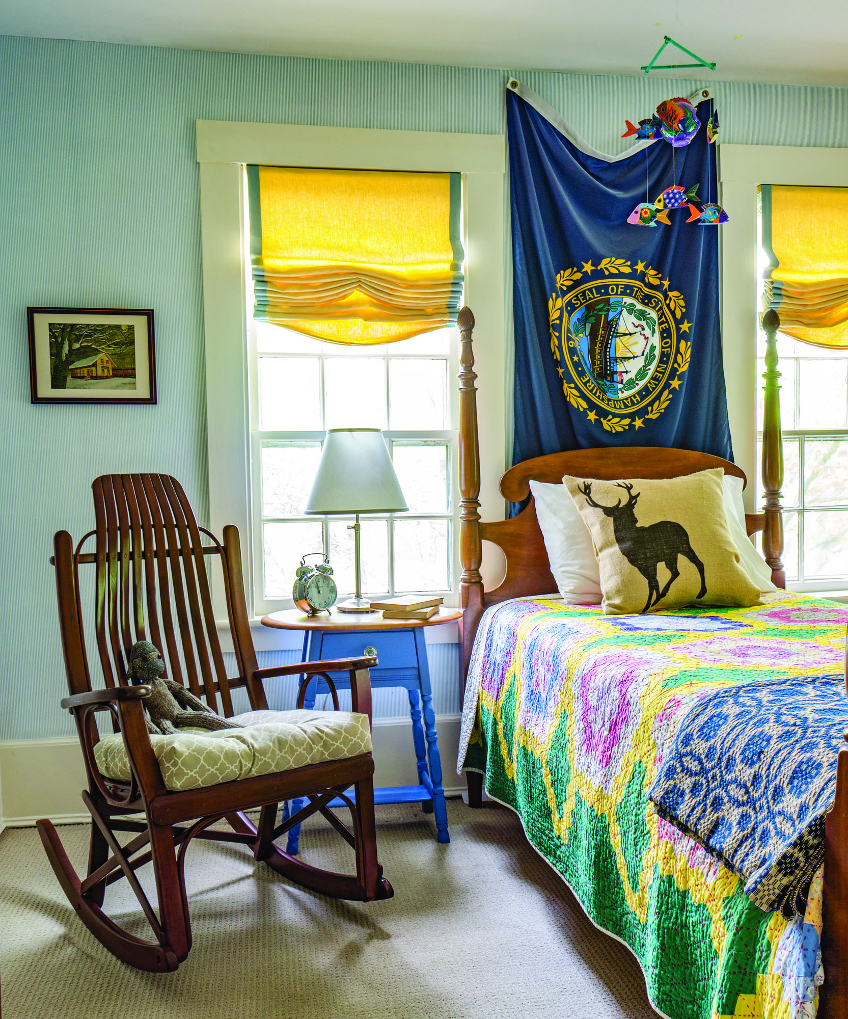 New Hampshire state flag softens the wall  behind the bed. The vintage rocker adds a rustic note.