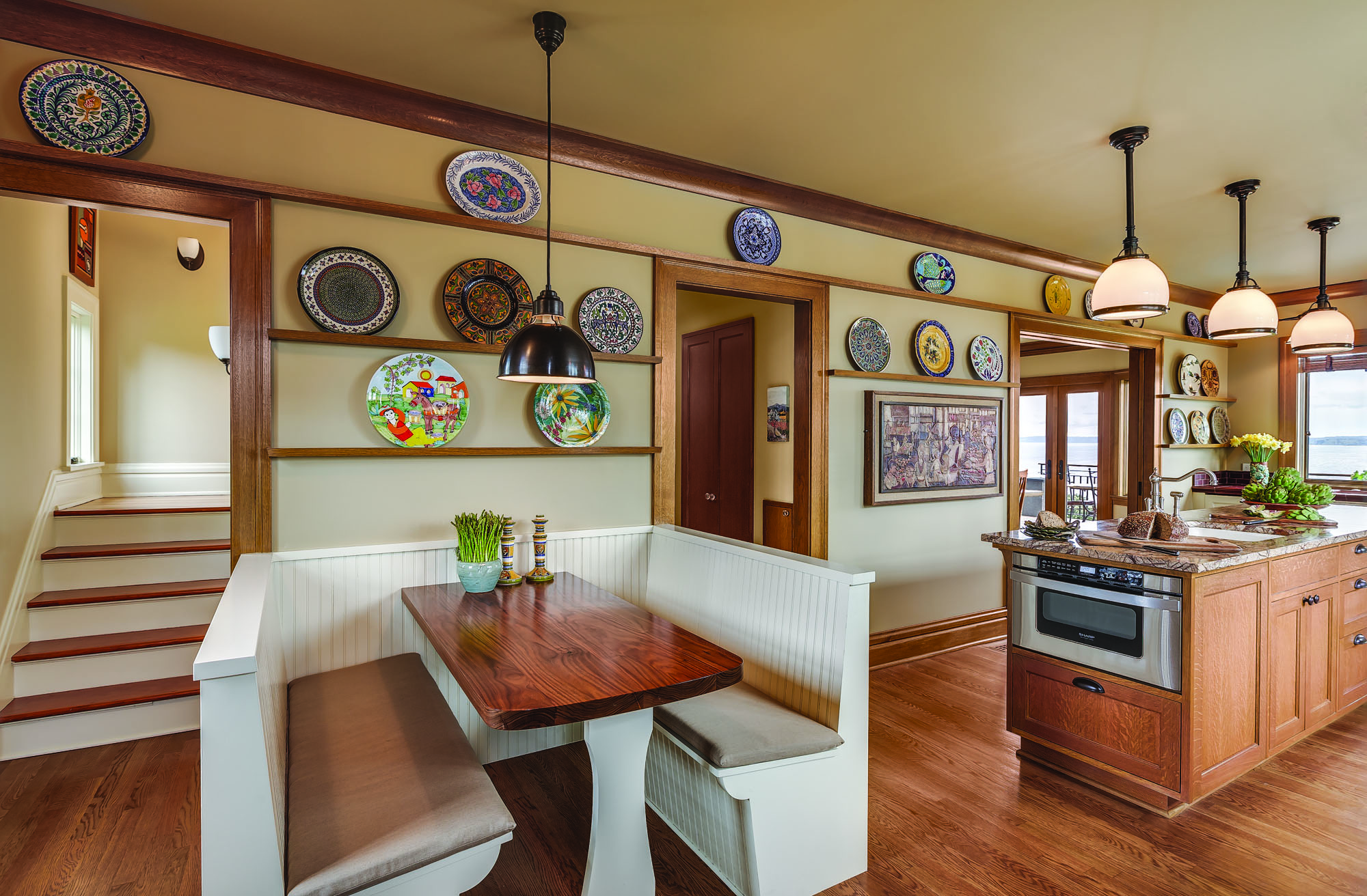 The banquette has a custom walnut tabletop; it's a quick step to the microwave oven at the end of the island. The back stairs are here; a pantry is in the main hall entry to the kitchen.