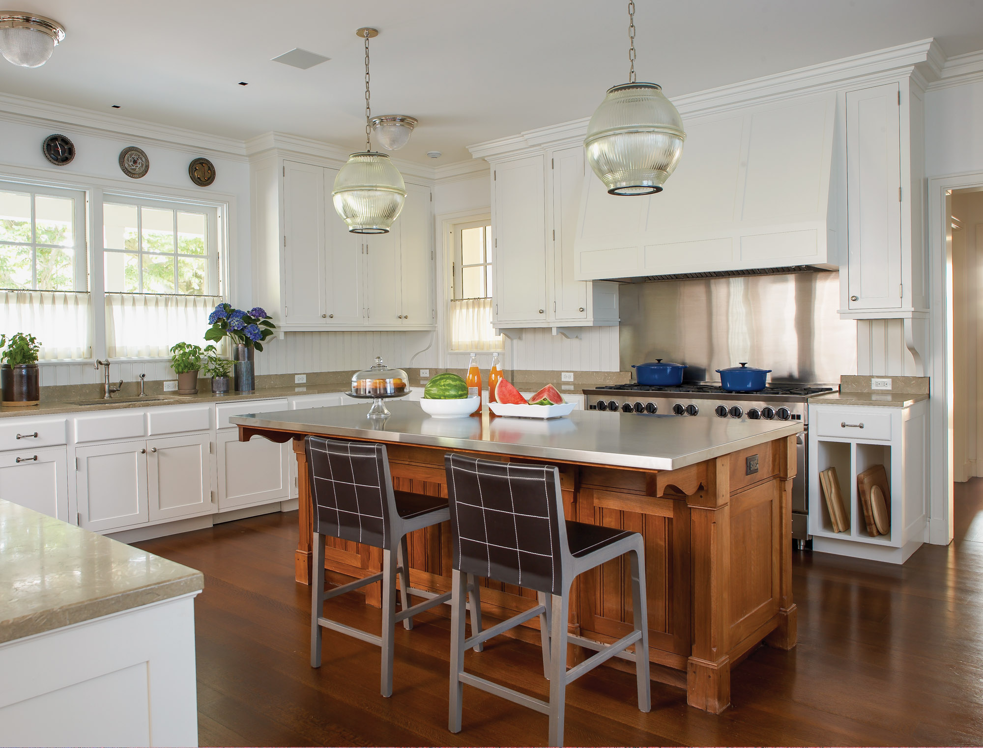 In purposeful contrast to the white-painted cabinets, the kitchen island has a natural wood finish. A large commercial range is perfect for a family who love to cook and entertain.