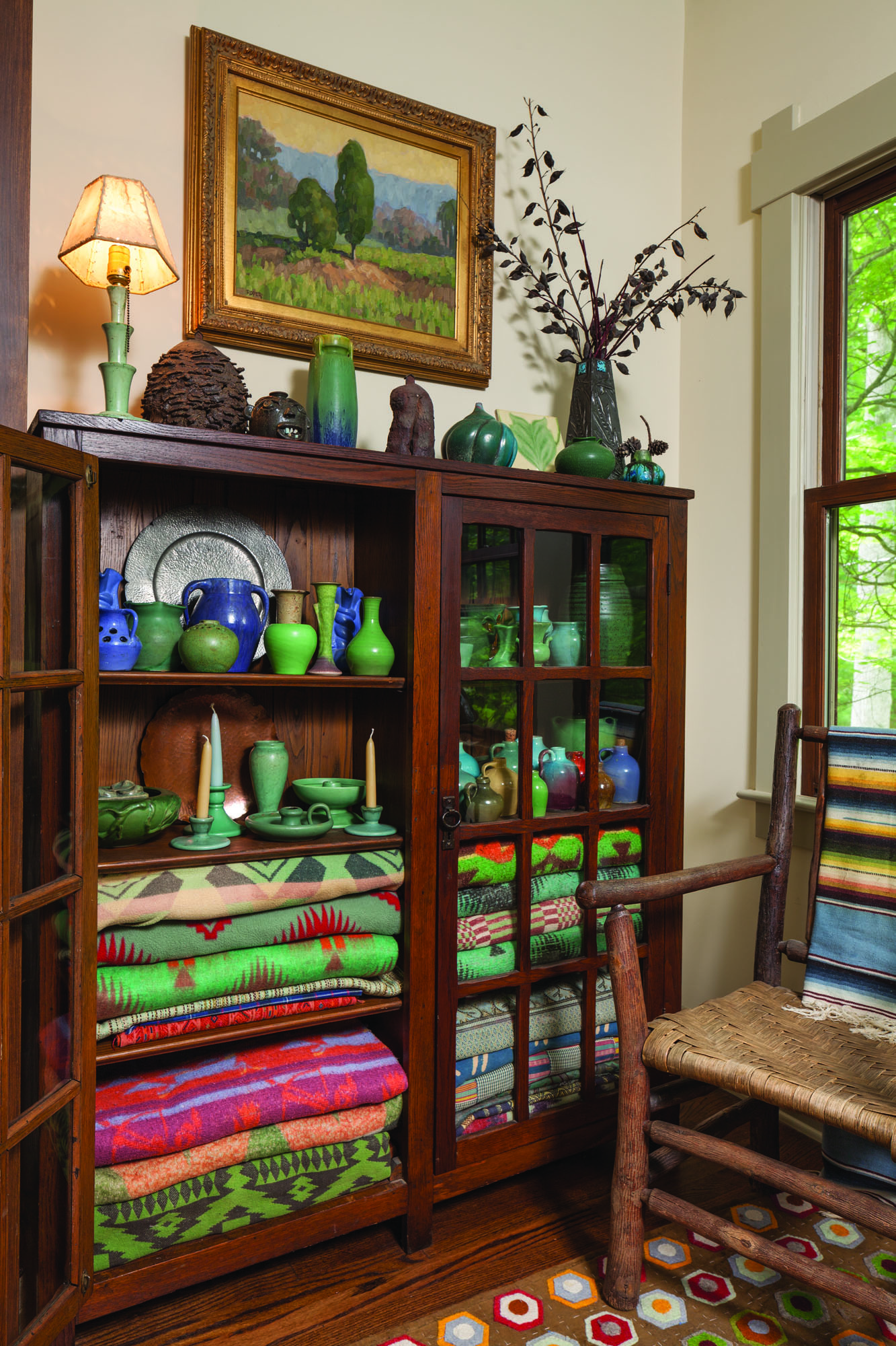 A bookcase in the study displays more of the owners' extensive collection of North Carolina ceramics, along with colorful camp blankets made by local textile mills.