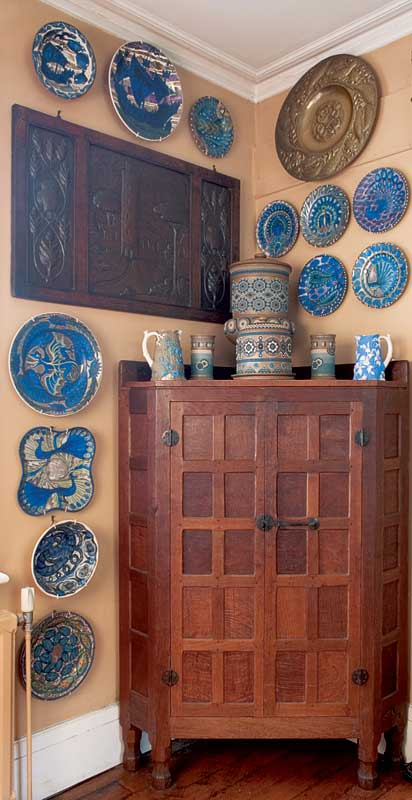 A cabinet for a corner; its warm wood patina suggested the peachy wall color, then plates in complementary blue. Photo: Duncan McNeill