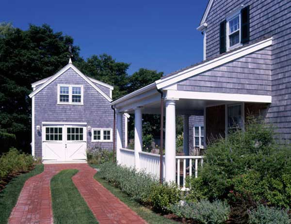 A classic double-track driveway runs to the detached garage; brick and weathered cedar shingles are ubiquitous on Nantucket. Photo: Peter Zimmerman Architects