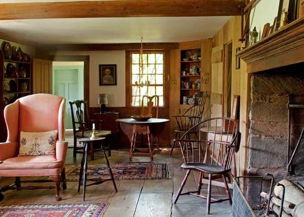 A collection of early American furniture adds to the ambience of what was once the all-purpose main room. Notice the large cooking fireplace and the original, wide-board floors.