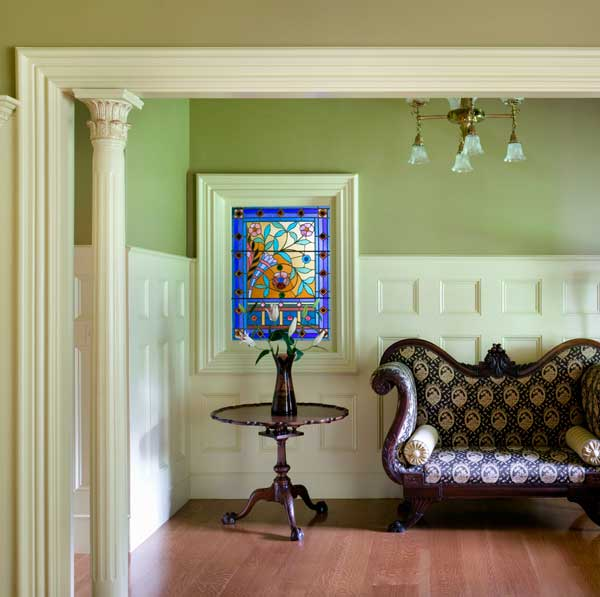 A curvaceous settee and a piecrust table are lit by one of many restored art-glass windows.